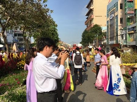 Nhiều người mặc áo dài truyền thống du xuân tại đường hoa sáng sớm mùng 1 Tết