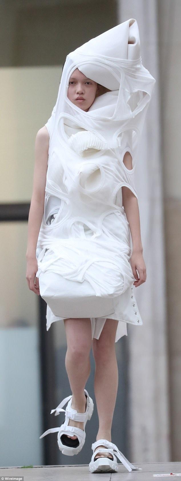 Các người mẫu trình diễn bên cạnh một đài phun nước. Các bộ trang phục họ trình diễn được ví như những tấm nệm chằng lại bằng ga trải giường đục lỗ.