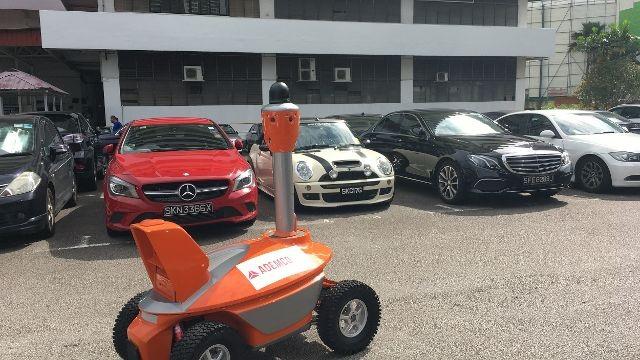 Robot bảo vệ đi tuần tại khu đỗ xe của một tòa nhà.