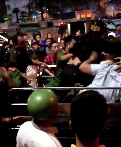 Lực lượng Cảnh sát giải cứu nhóm thanh niên bị người dân bao vây - Ảnh cắt từ clip.