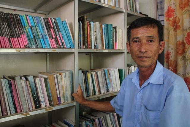 Ông Hưng bên những cuốn sách trong thư viện của mình