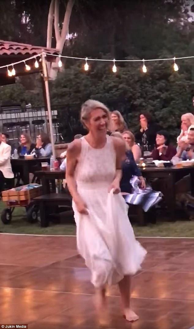 Cô dâu cười vui vẻ và nhìn ra khía cạnh hài hước của tình huống. Trong khi đó, hai người đàn ông tiến lại giúp chú rể đứng dậy.