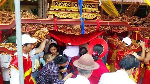 Người dân và du khách nô nức chui kiệu trong ngày lễ rước kiệu mừng lễ Phật đản ở huyện Kim Sơn, Ninh Bình.