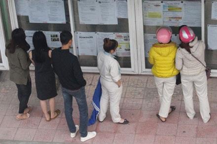 Nhiều người có nhu cầu tìm việc đang xem thông báo tuyển dụng tại cổng A KCN Bắc Thăng Long (Hà Nội).