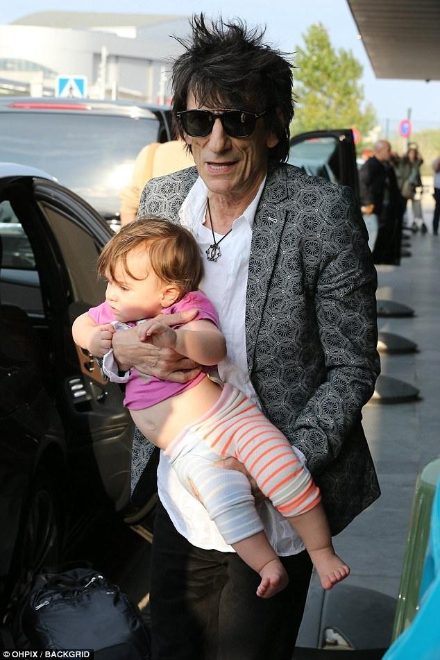 Ronnie Wood - Rocker kỳ cựu người Anh bế con gái 15 tháng tuổi tại sân bay Barcelona, Tây Ban Nha ngày 25/9 vừa qua