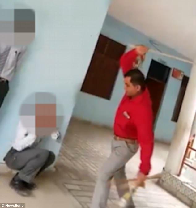 Thầy hiệu trưởng dùng roi đánh vào người học sinh ở Ấn Độ (Ảnh: Newslions)