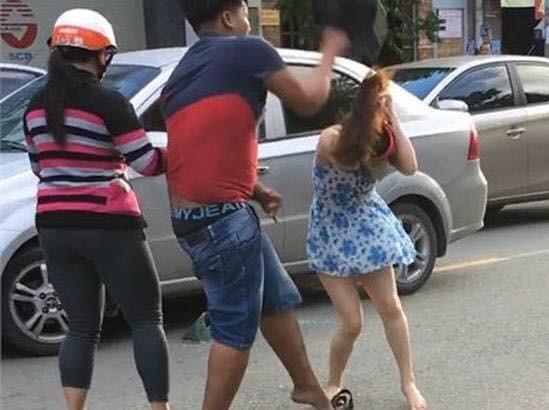 Người đàn ông dùng mũ bảo hiểm đánh vào đầu người phụ nữ (cắt từ clip).