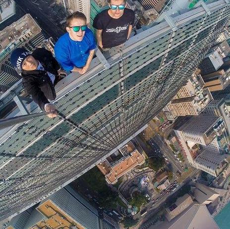 """Mặc dù chụp ảnh """"tự sướng"""" là trào lưu thu hút sự quan tâm của nhiều người, đặc biệt là giới trẻ, nhưng việc nhiều người bất chấp sự an toàn của bản thân chỉ nhằm mục đích ghi lại những hình ảnh ấn tượng cũng đang là vấn đề đáng lo ngại. Trong ảnh: 3 người đàn ông đứng trên nóc một tòa nhà cao tầng để chụp ảnh """"tự sướng"""". (Ảnh: Instagram)"""