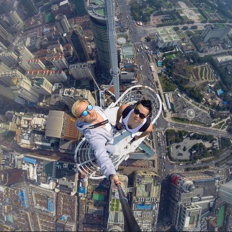 """Những tòa nhà chọc trời là điểm đến không thể bỏ qua của những người muốn chụp những bức ảnh """"không giống ai"""". Trong ảnh: Hai người đàn ông chụp ảnh """"tự sướng"""" trên nóc một tòa nhà cao tầng ở Thượng Hải, Trung Quốc. (Ảnh: Instagram)"""