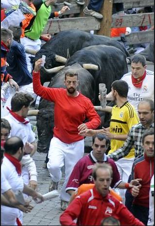 """Người đàn ông này thậm chí vừa chạy vừa chụp ảnh """"tự sướng"""" ngay trước mũi bò tót. (Ảnh: Getty)"""