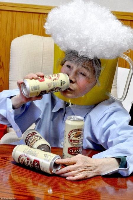 Cụ bà Nishimoto đội chiếc mũ hình cốc bia và đang thưởng thức những lon bia