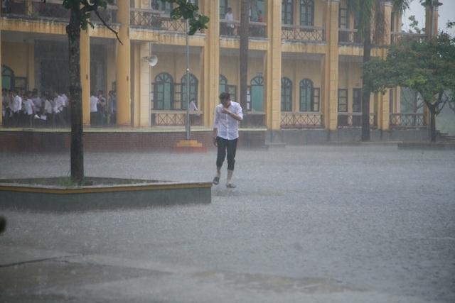 Thi sinh đội mưa ra khỏi điểm thi (ảnh: Đức Văn)