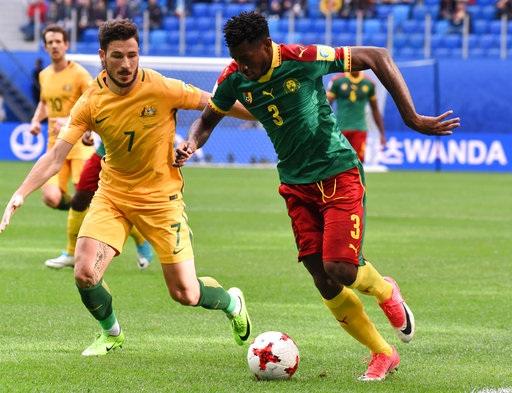 Zambo (Cameroon, phải) đi bóng trước sự truy cản của Leckie (Australia, trái)