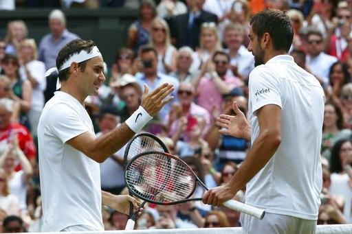 Federer (trái) nhận cái bắt tay chúc mừng từ Cilic (phải)