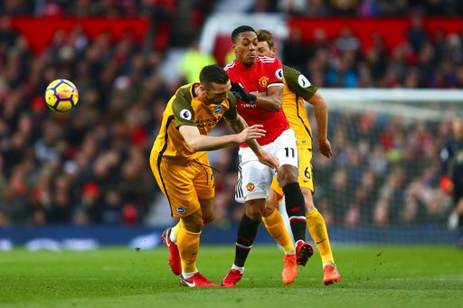 Martial (giữa) trong vòng vây của hai cầu thủ Brighton