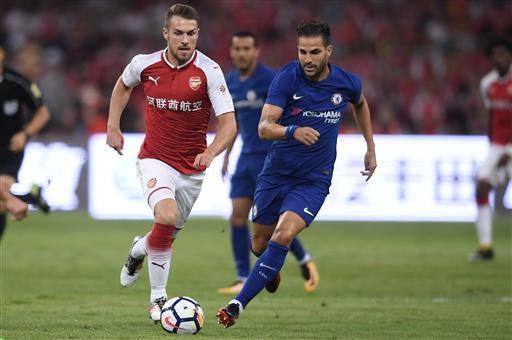 Ramsey (trái) đi bóng trước sự truy cản của Fabregas (phải)