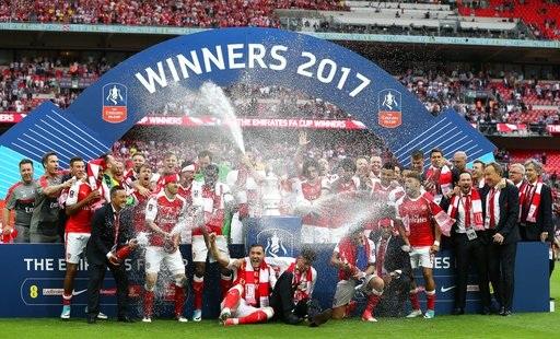 Các cầu thủ Arsenal bật champagne ăn mừng tại bục chiến thắng