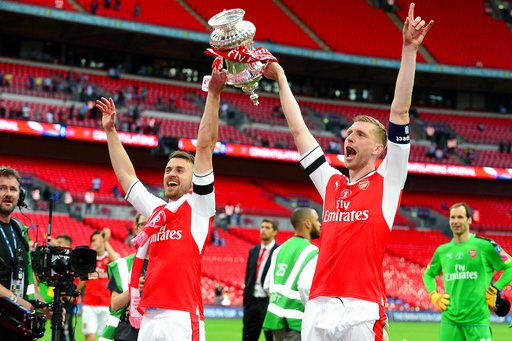 Ramsey (trái) và Metersacker (phải) giơ cao cúp FA. Tiền vệ người xứ Wales chính là người ấn định chiến thắng 2-1 cho Arsenal, trong khi hậu vệ người Đức đã chơi xuất sắc trong trận đấu đầu tiên đá chính sau 13 tháng.