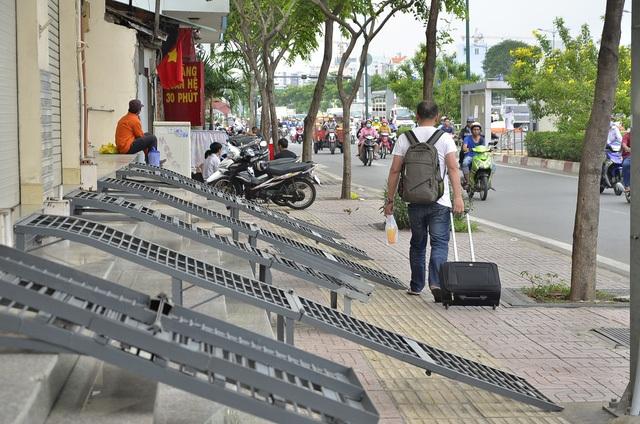 Trong khi cả nước đang rầm rộ với chiến dịch lấy lại vỉa hè cho người đi bộ thì ngay tại tuyến đường Phạm Văn Đồng - tuyến đường được xem là đẹp nhất Sài Gòn, vẫn tồn tại những bậc tam cấp bằng sắt dài đến 3m, vươn ra chiếm gần hết vỉa hè... (Ảnh: Đình Thảo)