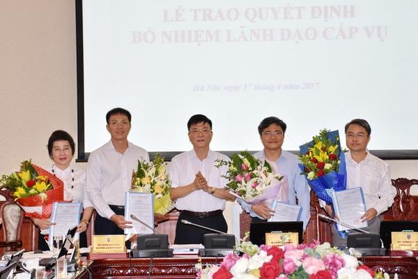 Bộ trưởng Lê Thành Long trao quyết định và tặng hoa chúc mừng những cán bộ được bổ nhiệm.