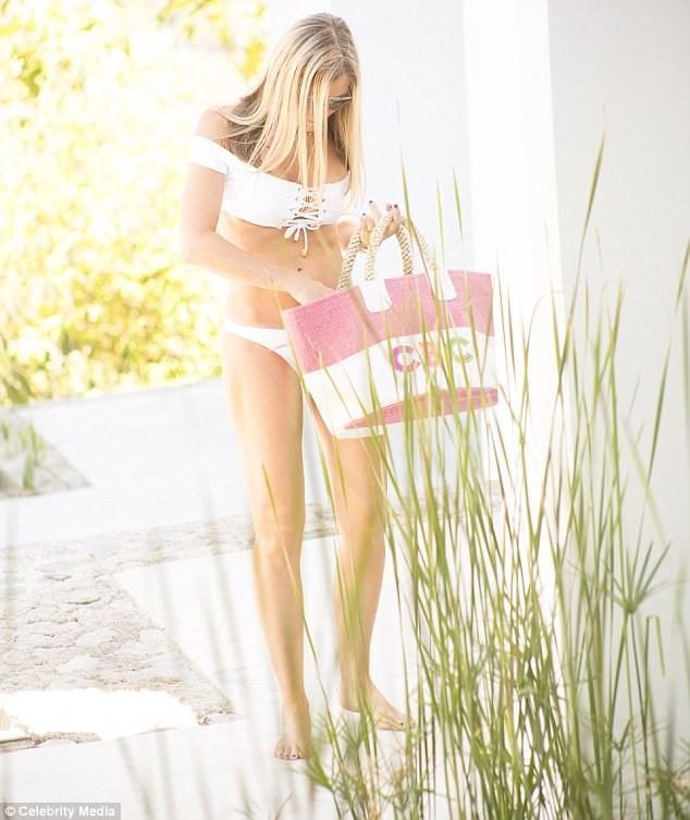 Caprice khoe đôi chân dài miên man và dáng vóc gợi cảm, thon thảo trong bộ áo tắm màu trắng tại khu resort cao cấp tại Ibiza.