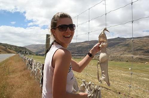 Một nữ du khách thích thú chụp hình tại hàng rào nội y