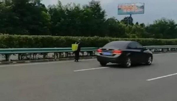 Hình ảnh cụ ông đi bộ ven đường cao tốc trước khi được lực lượng cảnh sát mời dừng lại để nói chuyện