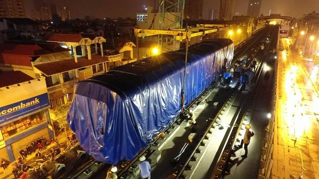 Sau nhiều giờ loay hoay, vào khoảng 2h45 ngày 21/2, chiếc cẩu bánh xích Kobelco CKS2500 (cần cẩu loại 250 tấn) đã đặt thành công toa tàu đầu tiên lên ray đường sắt Cát Linh - Hà Đông. (Ảnh: Mạnh Thắng)
