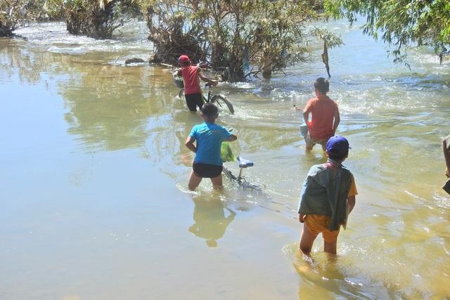Do cầu rụng gần hết, các em nhỏ phải lội qua dòng suối dữ hiểm nguy (ảnh: Đàm Quang)