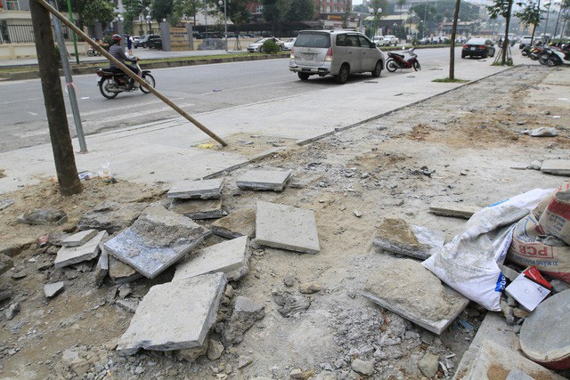 """Lãnh đạo các quận nội thành TP Hà Nội đã yêu cầu đơn vị thi công cạy những viên đá lát vỉa hè """"bền 70 năm"""" dọc các đường Nguyễn Trãi, Đền Lừ, Mỗ Lao… bị bong tróc, nứt gãy lên làm lại. (Ảnh: Quang Phong)"""