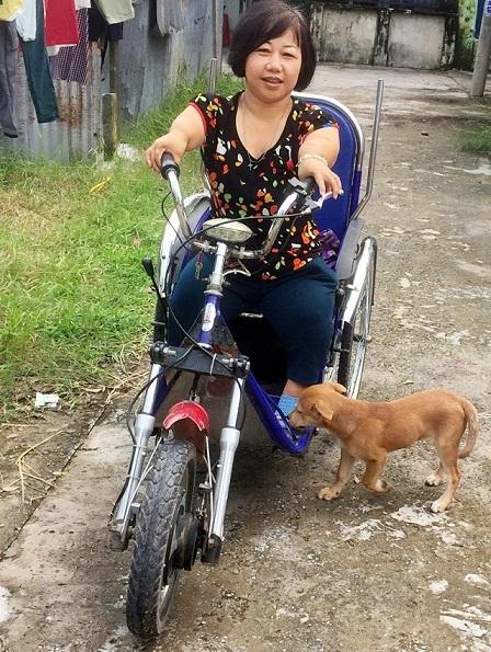 Chị Thơm trên chiếc xe lăn chạy bằng pin.