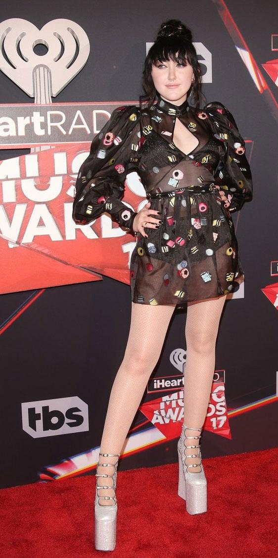 Noah Cyrus, em gái của Miley Cyrus, khoe chân thon với váy ngắn và giày cao gót đế bục.