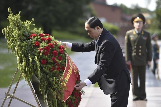 Chủ tịch nước Trần Đại Quang chỉnh vòng hoa tại đài tưởng niệm (Ảnh: Reuters)