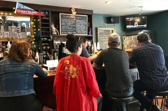 Mọi người chăm chú theo dõi cuộc điều trần tại một quán bar ở Brooklyn, New York (Ảnh: Reuters)