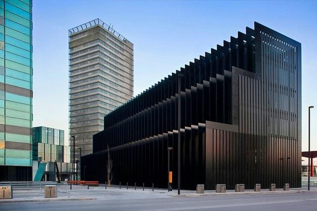 Khối kiến trúc sở hữu màu đen huyền bí này là trụ sở chính của tập đoàn Layetana. Được biết đây là một tòa nhà đặc biệt với cấu trúc hai lớp. Lớp bên ngoài chính là phần khung thép khổng lồ mà chúng ta có thể thấy trong ảnh. Lớp thứ hai ở bên trong lại được làm hoàn toàn bằng kính. Kiểu thiết kế này tạo ra hiệu ứng nhiệt cho tòa nhà giúp nó có khả năng tiết kiệm năng lượng.