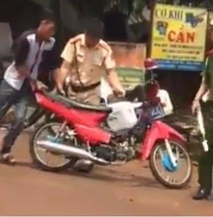 Nam thanh niên (áo trắng đen) bị CSGT kiểm tra vì điều khiển xe máy không đội mũ bảo hiểm