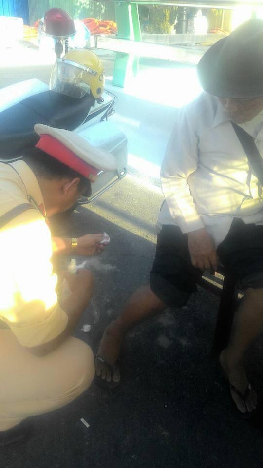 Cảnh sát giao thông Đà Nẵng rửa vết thương cho cụ ông bán vé số (ảnh Cảnh sát giao thông Đà Nẵng)