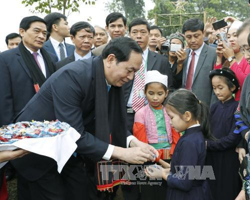 Chủ tịch nước Trần Đại Quang phát kẹo cho các cháu thiếu nhi dân tộc Thái tại làng dân tộc Thái (Điện Biên). Ảnh: Nhan Sáng-TTXVN
