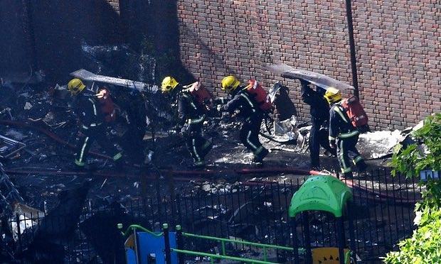 Lính cứu hỏa dùng khiên chắn để che đầu, tránh vật nặng rơi từ phía trên tòa tháp (Ảnh: EPA)