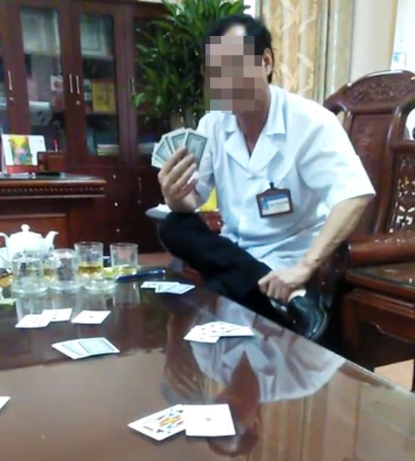 Hình ảnh ông Đ.T.B. mặc áo blouse trắng, ngồi đánh bài với cấp dưới ngay tại phòng làm việc.