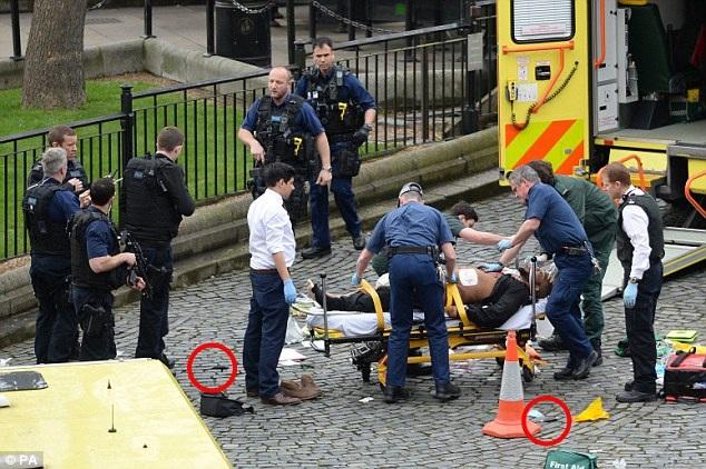 Sau khi lao xe vào hàng rào bên ngoài trụ sở quốc hôi, nghi phạm tiếp tục cầm dao vào khu vực tòa nhà và tấn công một sĩ quan cảnh sát làm nhiệm vụ gác cổng. Tên này đã đâm chết viên sĩ quan trước khi bị cảnh sát bắn hạ. Trong ảnh: Người đàn ông nằm trên xe cáng được cho là nghi phạm gây ra vụ tấn công. Bên dưới là hai con dao (vòng tròn đỏ) nghi được sử dụng để gây án. (Ảnh: PA)