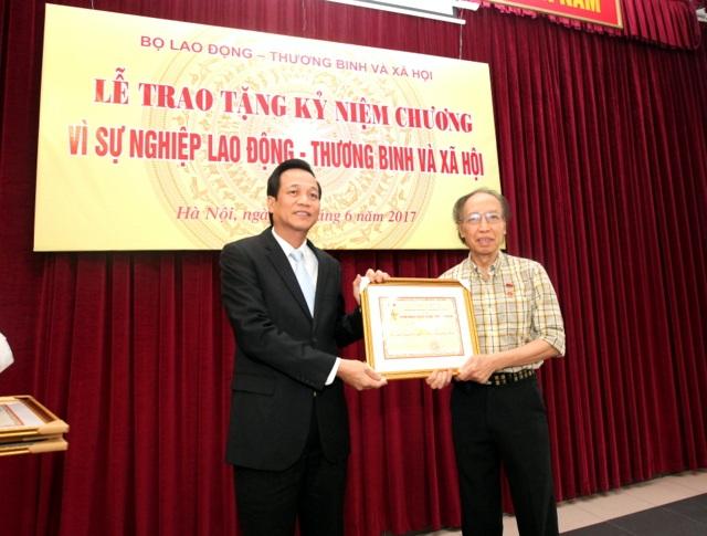 Bộ trưởng Đào Ngọc Dung (bên trái) tặng Kỷ niệm chương tới Tổng Biên tập Báo điện tử Dân trí Phạm Huy Hoàn (Ảnh: Mạnh Dũng)