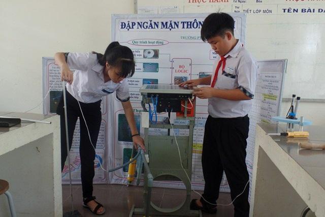 Hai em Huỳnh Hoàng Khánh và Nguyễn Thị Ngục Dung bên sản phẩm của mình sáng chế