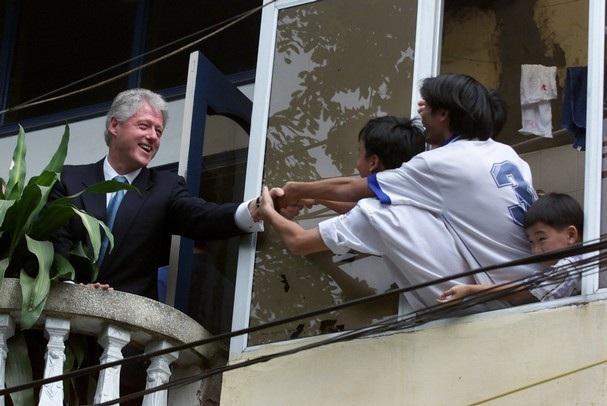 Tổng thống Bill Clinton bắt tay người dân Việt Nam trên ban công một ngôi nhà đối diện Văn Miếu – Quốc Tử Giám, vào ngày 17/11/2000. Cuối năm 2001, Hiệp định thương mại song phương Việt - Mỹ có hiệu lực (ảnh: AP)