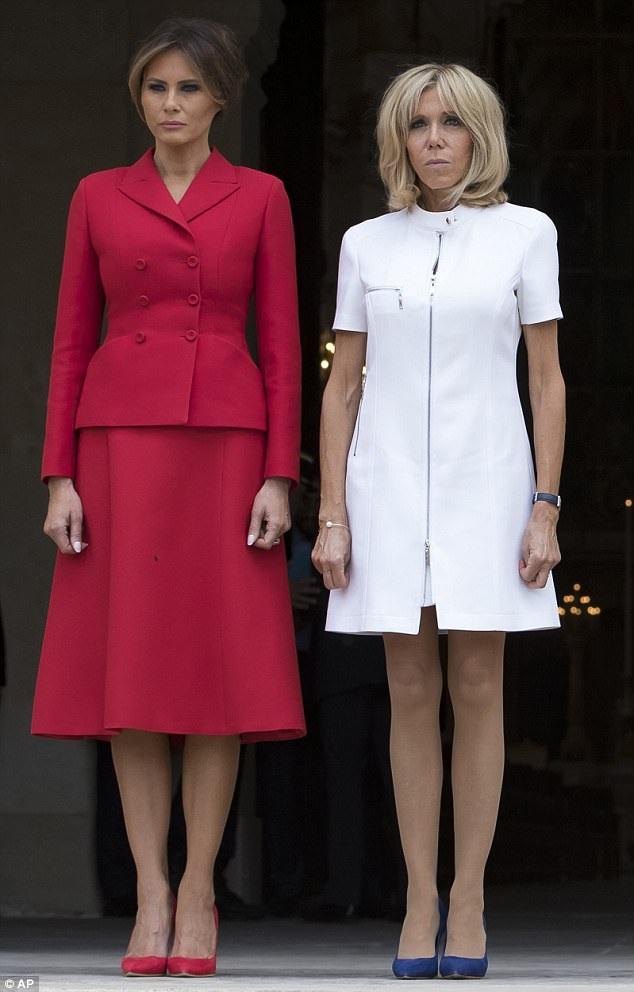 Bà Melania chọn bộ trang phục đỏ nổi bật của hãng thời trang Christian Dior khi tham dự các hoạt động đầu tiên cùng chồng tại Paris, trong khi bà Brigitte mặc thiết kế của nhà mốt danh tiếng Louis Vuitton (Ảnh: AP)