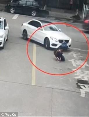 Ảnh chụp từ clip cho thấy cậu bé ngồi buộc dây giày giữa đường