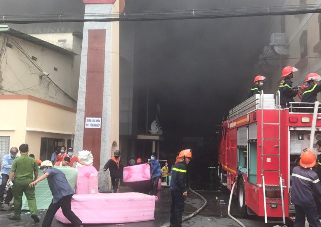 Lính cứu hỏa di dời tài sản của công ty ra khỏi hiện trường