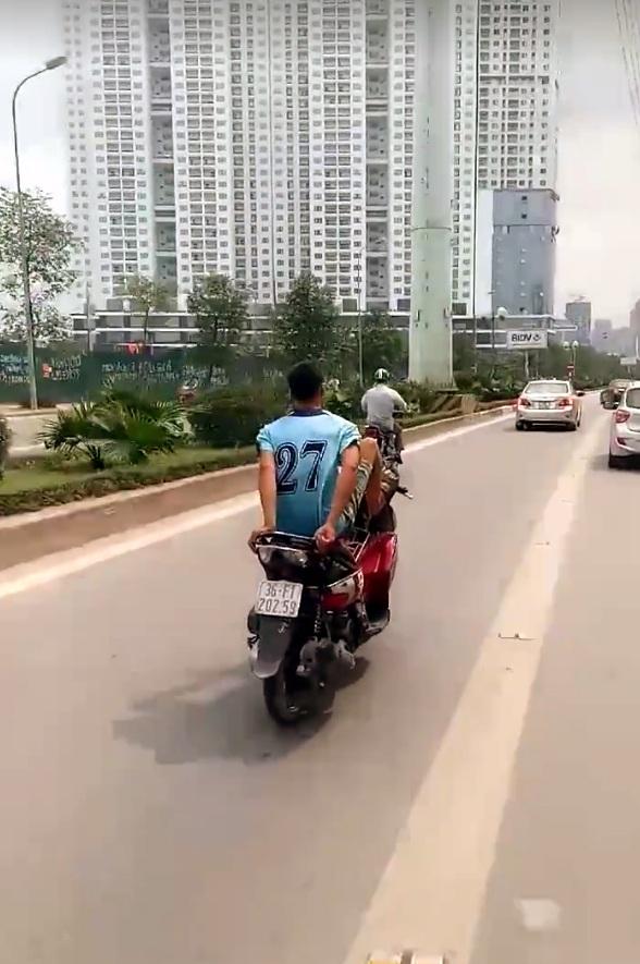 Nam thanh niên trổ tài điều khiển xe máy bằng chân. (Ảnh cắt từ clip)
