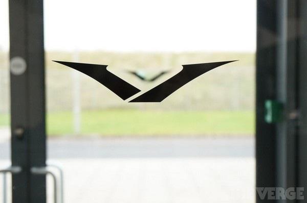"""Logo hình chữ """"V"""" của Vertu được in trên cửa ra vào của nhà máy. Ban đầu logo của Vertu được thiết kế theo dạng 2 cánh tay đang dang ra, tuy nhiên sau đó logo này đã thay đổi do được nhận xét giống với logo hãng xe Mazda của Nhật Bản."""