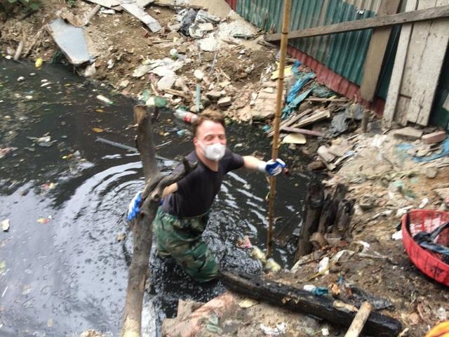 Hình ảnh người nước ngoài nhặt rác dưới mương được nhiều người chia sẻ. (Ảnh: Internet)